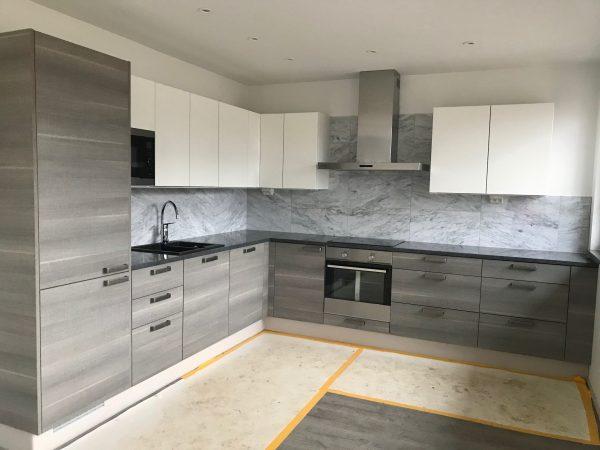 Keittiön taustassa Bianco Carrara C marmorilaatta koossa 610x305x10.
