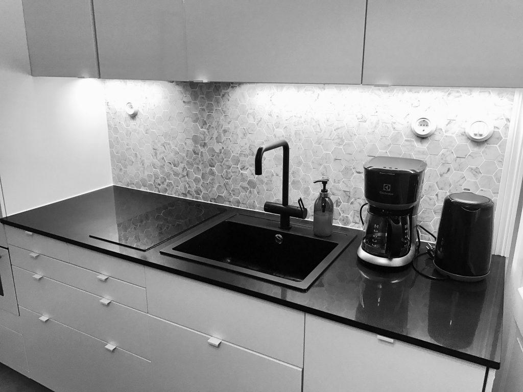 kuusikulmaista marmoria keittiön välitilassa. Tasona musta kvartsikivitaso. Vaaleat pienivetimiset kaapit.